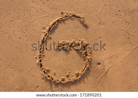 G text written in the sandy on the beach - stock photo