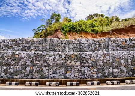 Gabion wall made of stones in the steel mesh, used as a fence on a slope. - stock photo
