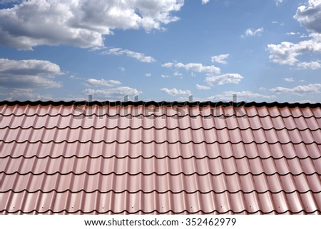 Gable roof of a house covered with metal tile closeup against blue sky with white clouds