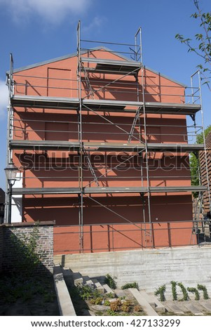 Gable scaffolding at a residential building currently under construction and painting. Ribe, Denmark. - stock photo
