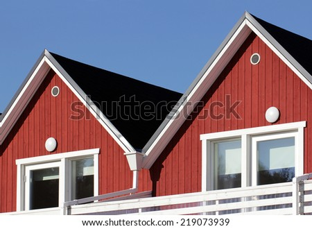 Gables of wooden Scandinavian house  painted in traditional white and red colors against deep blue sky. - stock photo