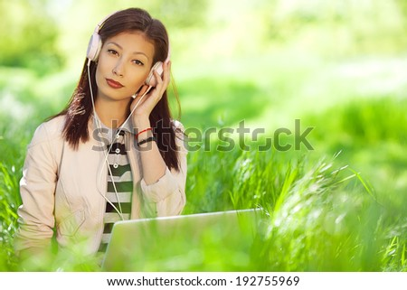 Gadget freak concept. Portrait of fashionable hipster girl in pink leather jacket listening to music on pc, sitting in green grass in the park. Sunny day. Close up. Copy-space. Outdoor shot - stock photo