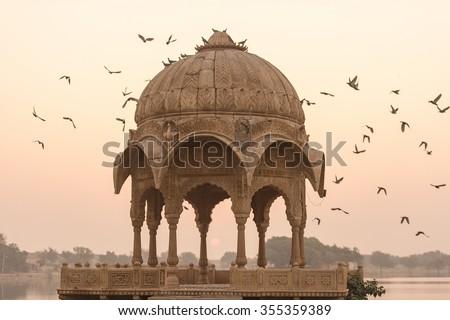 Gadi Sagar temple in Gadisar lake during sunrise. The temple and the lake located at Jaisalmer, Rajasthan, North India. - stock photo