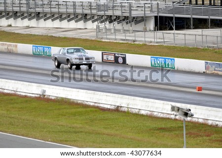 GAINESVILLE, FL - DECEMBER 6: A gray car racing on the track at the Buick, Oldsmobile, Pontiac, and Cadillac Florida Finals at the Gainesville Raceway on December 6, 2009 in Gainesville, FL.