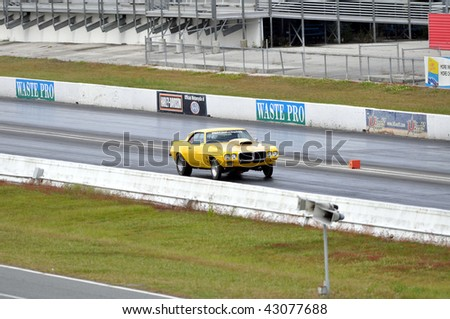 GAINESVILLE, FL - DECEMBER 6: A yellow car on the track at the Buick, Oldsmobile, Pontiac, and Cadillac Florida Finals at the Gainesville Raceway on December 6, 2009 in Gainesville, FL.