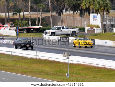 GAINESVILLE, FL - DECEMBER 6: From left, # 18, the driver of a black Pontiac racing against # 10 Tony Pawlish racing his 2004 Pontiac GTO at the NHRA Gainesville Raceway on December 6, 2009.