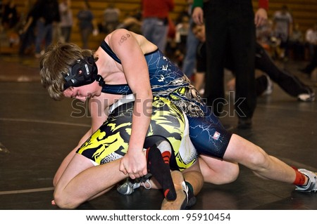 GAINESVILLE, GA, USA - FEB 11: Andy Leggett, the winner, holds an unidentified opponent in the 11-14 division of a wrestling tournament, February, 11, 2012, North Hall High School in Gainesville, GA. - stock photo