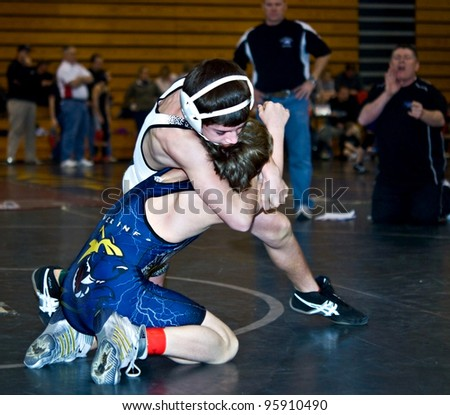 GAINESVILLE, GA, USA - FEB 11: Andy Leggett, winner, is held by an unidentified boy in the 11-14 division of a wrestling tournament, February, 11, 2012, at North Hall High School in Gainesville, GA.