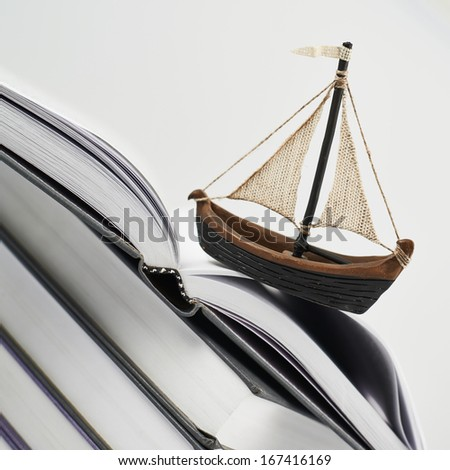 Gaining knowledge concept as a tiny boat over an opened book's page composition - stock photo