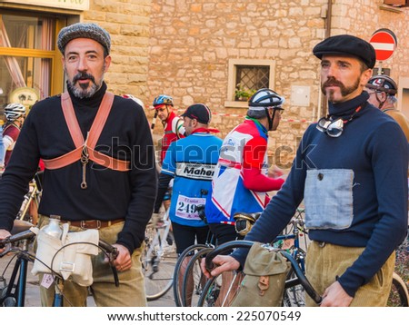GAIOLE IN CHIANTI, ITALY - 5 OCT. 2014: Unidentified participants of L'Eroica, a historic cycling event for owners of vintage bicycles and apparel who ride through Tuscany on white gravel roads. - stock photo