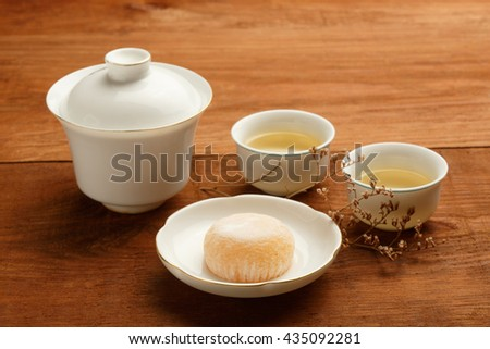 Gaiwan and cups of white chinese porcelain with green tea standing on wooden table with delicious japanese mochi rice cake on white plate, decorated with dried flower. Shallow dof, focus on foreground - stock photo