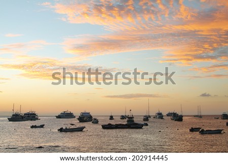 GALAPAGOS, ECUADOR - APRIL 29: Sunset view of boats of Puerto Baquerizo Moreno on April 29, 2014 in San Cristobal island. Puerto Baquerizo is one of only 3 inhabited port cities in Galapagos island.
