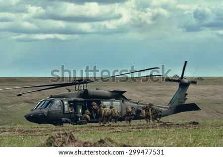 GALATI, ROMANIA - 09 APRIL: UK special forces elite demonstrating evacuation skills during combat using a UH-60 Black Hawk helicopter at the military poligon in April 09, 2015 near Galati, Romania - stock photo