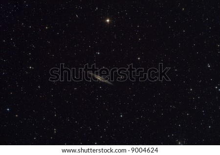 Galaxy NGC891 surrounded by stars - stock photo
