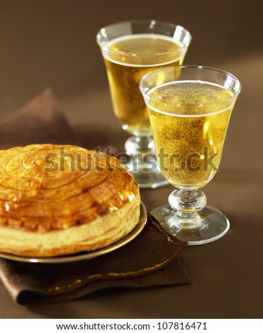 Galette des rois and glasses of cider - stock photo