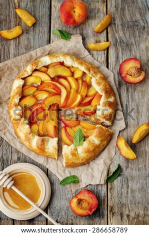 Galette with peaches on a dark wood background. the toning. selective focus - stock photo