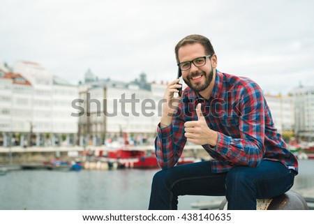 Galician Young bearded man talking on cellphone outdoors at an urban harbour doing success thumbs up sign, in A Coruña, Galicia. - stock photo