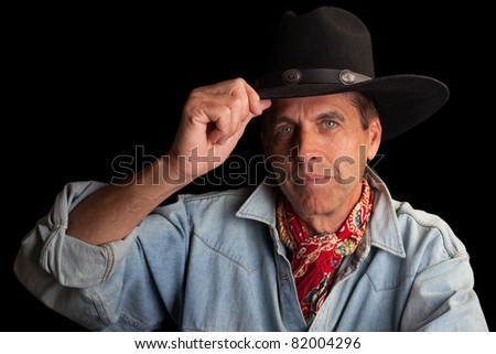 Gallant gentleman in cowboy outfit tipping his hat.