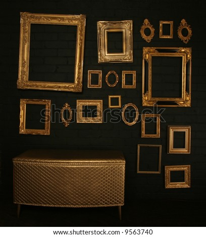 Gallery display - vintage gold frames and a chest on a black brick wall, similar available in my portfolio - stock photo