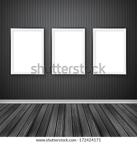 Gallery interior with three empty frames on wall. - stock photo