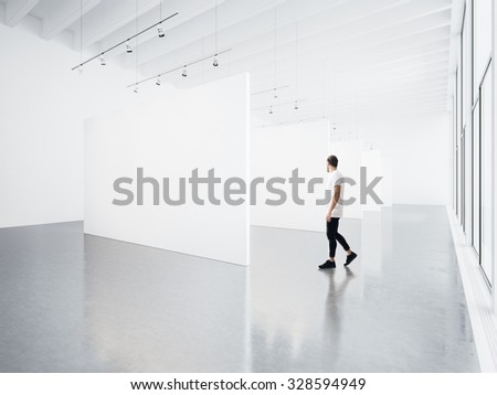 Gallery interior with white canvas and young man.  - stock photo