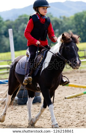 Gallop, horseback riding, lovely equestrian - young girl is riding a pony - stock photo