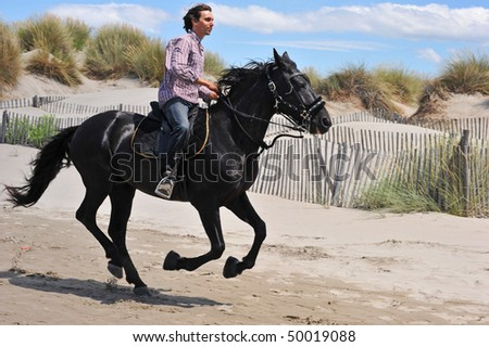 galloping black stallion and his rider on the beach - stock photo