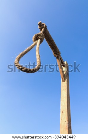 Gallows and hangman noose against a blue sky