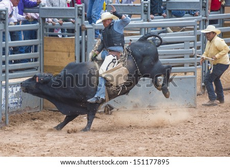 GALLUP , NEW MEXICO - AUGUST 10 : Cowboys Participates in a bull riding Competition at the 92nd annual Indian Rodeo in Gallup, NM on August 10 2013   - stock photo