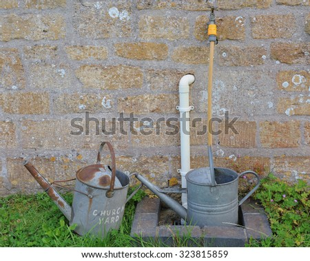 Galvanized Metal Watering Cans, one with Church Yard Painted on the Side, by the Church  in the Parish of St Margaret of Antioch, Tintinhull, Somerset, England, UK - stock photo