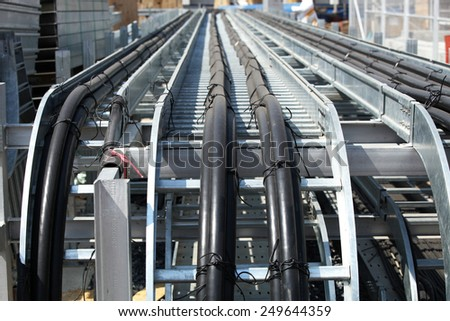 Galvanized steel rack for power cables under installation. - stock photo