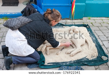 GALWAY, IRELAND - JULY 29, 2009: Street artist working on a sand sculpture of dogs. The Galway Arts Festival takes place in July and is one of the biggest arts festivals in Ireland.