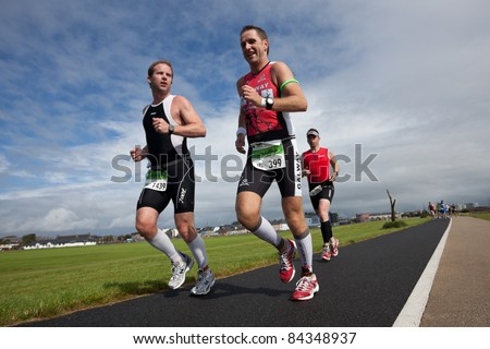 GALWAY, IRELAND - SEPT 4: John Cullinan (399) and Gavin Mcallister (1439) compete at first Edition of Iron Man  Triathlon on September 4, 2011 in Galway, Ireland - stock photo