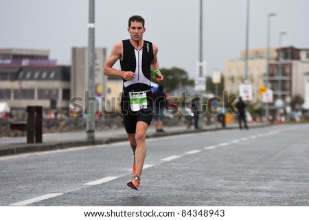 GALWAY, IRELAND - SEPT 4: Owen Cummins (12) , III place, competes at first Edition of Galway Iron Man Triathlon on September 4, 2011 in Galway, Ireland - stock photo