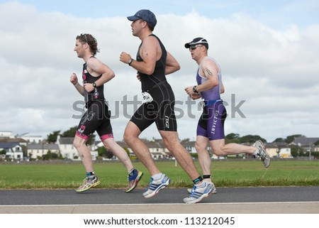 GALWAY, IRELAND - SEPTEMBER 2: Conor MacGuinness (316) and other athletes competing at Course-Run, during 2nd Edition of the Ironman 70.3 Galway 2012 Triathlon,on September 2, 2012 in Galway, Ireland. - stock photo