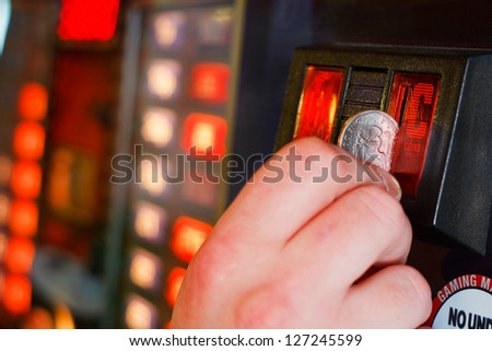 Gambler inserts dollar into slot machine - stock photo