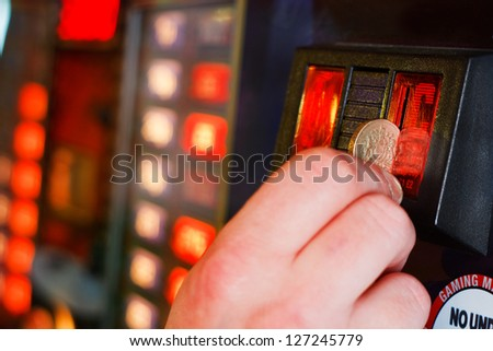 Gambler Inserts pound coin into gambling machine at casino - stock photo