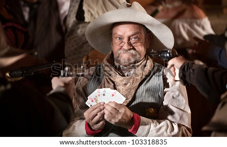 Gambler with cards and players guns pointed at him - stock photo