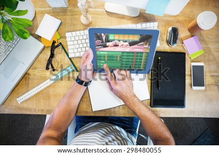 Gambling app screen against casual businessman working on tablet - stock photo