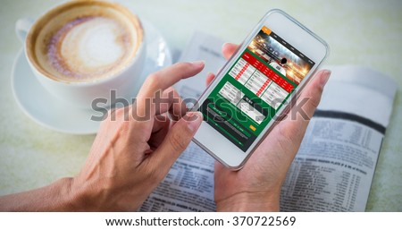Gambling app screen against man using mobile phone by coffee and newspaper in cafe - stock photo