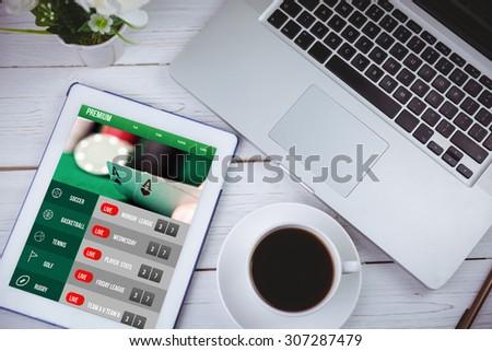 Gambling app screen against tablet on desk - stock photo