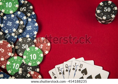 Gambling chips and card for poker on red felt background - stock photo
