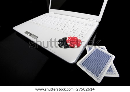 Gambling chips and cards on white laptop computer. - stock photo