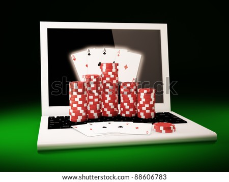 Gambling chips and poker cards on a laptop - stock photo