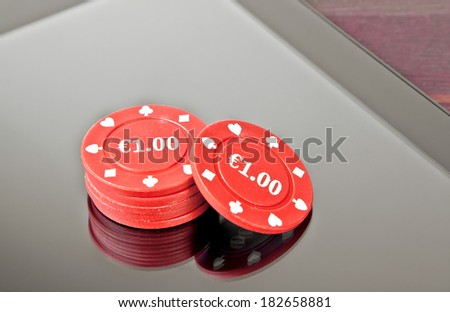 gambling chips on digital tablet pc on old wood table, concept of texas game on-line - stock photo