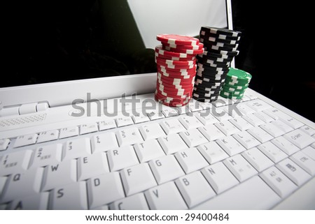 Gambling chips on white laptop computer. Online poker Concept