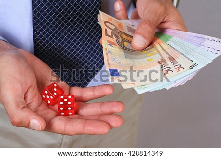 Gambling connect. Man winner holding money and gambling dice.  - stock photo