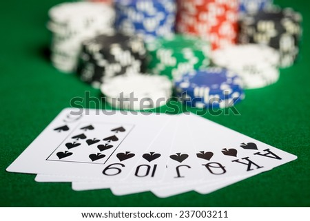 gambling, fortune, game and entertainment concept - close up of casino chips and playing cards on green table surface - stock photo