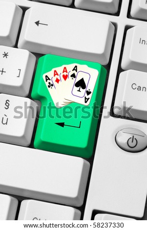 gambling on internet - casino on line - keyboard with aces poker on green enter key - stock photo