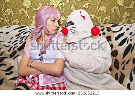 Game characters looking to each other. Cosplay characters on the sofa. Shot indoors  - stock photo
